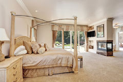 Large master creamy tones bedroom in luxury home. Royalty Free Stock Photos