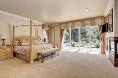 Large master creamy tones bedroom in luxury home. stock image