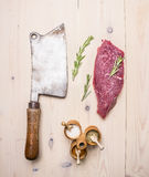 Large meat cleaver, with beef steak, rosemary and various spices wooden rustic background top view close up. Large meat cleaver, beef steak, rosemary and various stock photography