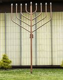 Menorah outside infront of a temple. A large medal menorah on the grass outside of a temple to celebrate the holidays stock image