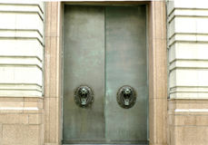 Large metal doors with lion handles. Large metal doors with roaring lion head handles in Liverpool UK stock photo
