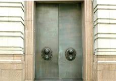 Large metal doors with lion handles. Large metal doors with roaring lion head handles in Liverpool UK Stock Photo