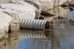Large metal drain pipe leading out into natural lake Stock Images