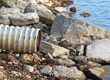 Large metal drain pipe on rocky shore line of lake Stock Photography