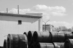 Large metal industrial barrels piled up and stacked on each other in black and white royalty free stock photos