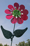 Large metal pinwheel. In the shape of a pink daisy with green leaves against a pale blue sky Royalty Free Stock Images