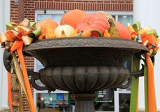Large metal urn with Fall`s cornucopia of pumpkins, squash and gourds Stock Photo