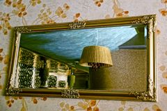 A large mirror on the wall and a chandelier on the ceiling in reflection Royalty Free Stock Photography