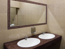 A large mirror in washroom public toilet.  Stock Images