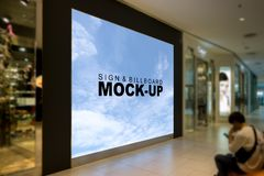 Mock up Sign or Billboards inside the mall. A large mock up blank billboard for advertising in front of the store inside the mall with young man sitting on the Royalty Free Stock Photos