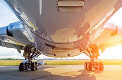 Large modern airplane view from bottom to bottom and landing gear, light sun Royalty Free Stock Photos