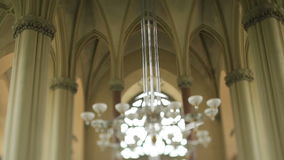Large modern chandelier in the nave of old gothic church. Large modern chandelier in old gothic church stock video footage