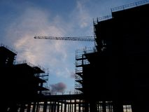 Large modern construction site in silhouette with scaffolding and railings covering the structure with crane in the background. Taken in the evening Stock Photos