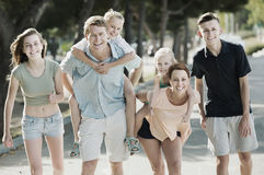 Large modern family walking with kids on parents back in summer Stock Photography