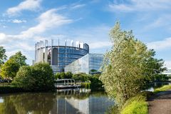 Large modern headquarter of European Parliament. In Strasbourg with boat stop and calm flowing Ill river and passerelle to the old building stock photos