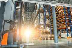 Large modern industrial logistic warehouse with forklifts, sunlight. Toned Royalty Free Stock Images
