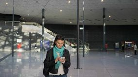 Main hall of the train or bus station. Large modern main hall or lobby of the train or bus station, airport with hurrying passengers, the girl waits for her stock video footage