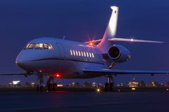 Large modern private business jet ready to take off at night. Private business jet with lights on waiting to take off at night stock image