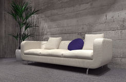 Large modern sofa in front of a cement brick wall Stock Photo