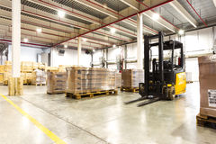 Large modern warehouse with forklifts. New Large modern storehouse with some goods Stock Photos