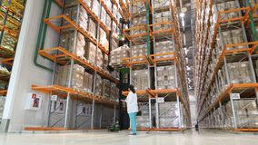 Large modern warehouse with forklifts. Warehouse worker taking package in the shelf in a large warehouse in a large Royalty Free Stock Photo