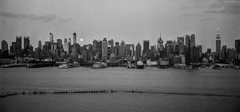 Large Moon Skyline Panorama. NEW YORK-AUGUST 10-A black and white panoramic film photograph of the New York City Skyline with the large moon on August 10 2014 royalty free stock image