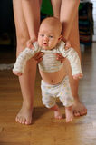 The large mother of experienced mother helps the baby. To make the first steps in his life stock images