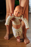 The large mother of experienced mother helps the baby to. Make the first steps in his life stock images