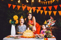 A large mother and three children at a festive table with sweets and a cake in the courtyard decorated with lights and a garland o royalty free stock photos