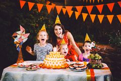 A large mother and three children at a festive table with sweets and a cake in the courtyard decorated with lights and a garland o stock photos