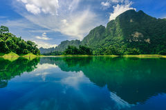 Large mountain with blue sky and reflection from the water. Royalty Free Stock Photo