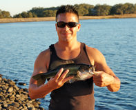 Large Mouth Bass. Image of male holding large mouth bass in front of lake Stock Photos