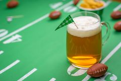 Large glass mug of cold beer on table with superbowl party decor. Large mug of cold beer on table at big game day celebration stock photos