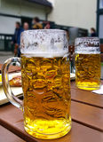 Large mugs of Bavarian beer at beer garden Stock Photography