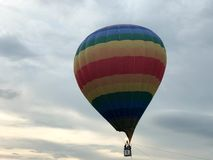 Large multi-colored bright round rainbow colored striped striped flying balloon with a basket against the sky in the evening stock photography