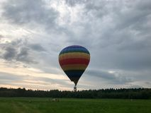 Large multi-colored bright round rainbow colored striped striped flying balloon with a basket against the sky in the evening stock images