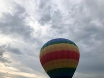 Large multi-colored bright round rainbow colored striped striped flying balloon with a basket against the sky in the evening royalty free stock photos
