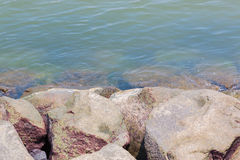 Large natural boulders  on blue water. Royalty Free Stock Image