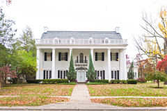 Large Neo-Classic Style Home. Large Neo-Classical style American home with white brick and a large porch lined with columns Royalty Free Stock Photos