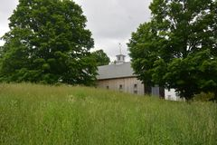 Large New England Barn setback in trees in Groton MAx. Light colored wooden set back in oak trees in grass covered field stock photo
