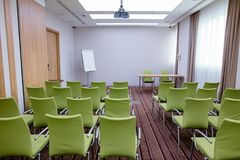 Large new meeting room with rows of modern green chairs. Flipchart, desk and video projector on the ceiling Royalty Free Stock Photos