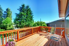Large new wood deck home exterior with chairs. Royalty Free Stock Photography
