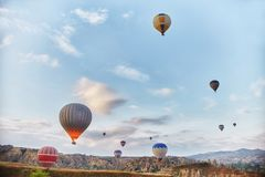 Large number of balloons fly in morning in the sky in rays of the dawn sun. Balloons balloons in the sky in the clouds Stock Image