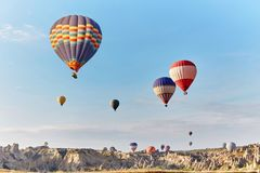 Large number of balloons fly in morning in the sky in rays of the dawn sun. Balloons balloons in the sky in the clouds Royalty Free Stock Photography