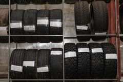 A large number of car wheels with tires stored vertically in racks for storage during a seasonal climate. Auto service stock image