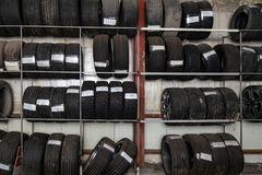 A large number of car wheels with tires stored vertically in racks for storage during a seasonal climate. Auto service royalty free stock photo