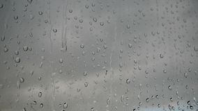 Large number of drops from the rain on the window glass. Stream of water swiftly flow down the glass. stock footage