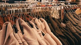 Large number of new warm stylish sweaters of different colors hanging on hangers in the clothing store shopping center. A large number of new warm stylish stock footage