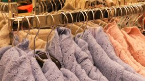Large number of new warm stylish sweaters of different colors hanging on hangers in the clothing store shopping center. A large number of new warm stylish stock video footage