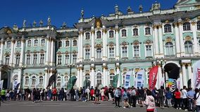 A large number of people stand at the facade of the Winter Palace in St. Petersburg Hermitage Museum. Spectators watch the SPb